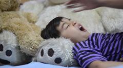 Little boy sleeping in bed on big bear doll Stock Footage