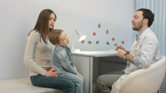 Doctor talking to young child and mother Stock Footage