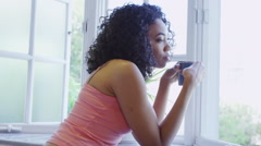 African woman standing by window with mug Stock Footage