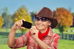 Aged cowgirl taken a picture of herself - stock photo
