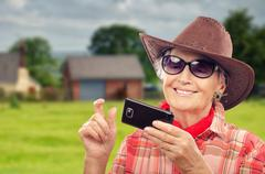 Aged cowgirl smartphone user surfing the internet - stock photo