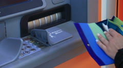 A woman receiving money from the ATM Stock Footage