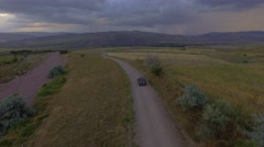4k aerial footage of a car chase on dirt road at the sunset. - stock footage