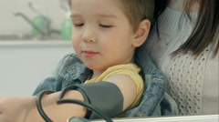 A medical worker taking a young boy's blood pressure Stock Footage