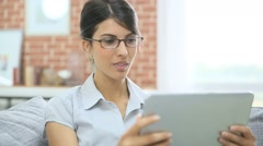 Young woman with eyeglasses websurfing on digital tablet - stock footage