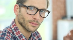 Portrait of smiling handsome guy taking his glasses off Stock Footage