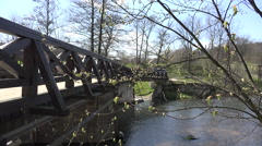First spring green leaves on tree twig and bridge over river. 4K Stock Footage