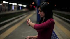 Young woman at night in train station waiting for boyfriend excited Stock Footage