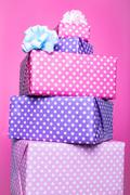 Colorful gift boxes with ribbon over pink background. purple, pastel, bright Stock Photos