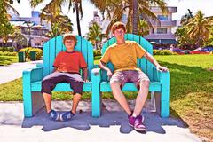 two brothers are sitting on a art deco park bench in south Miami - stock photo