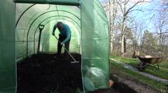 Farmer man leveling soil with rake tool in greenhouse. 4K Stock Footage