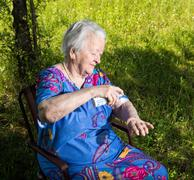 Old woman spraying insect repellent - stock photo
