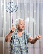 Old angry woman threatening with a carpet beater - stock photo