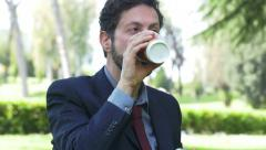 Young businessman using smartphone and drinking a coffee take away Stock Footage