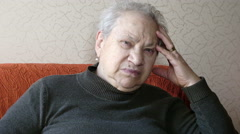 Sad and pensive old woman sitting on the sofa Stock Footage