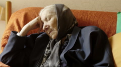 Depressed and desperate old woman sitting alone in her house Stock Footage
