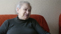 Pensive old woman sitting on the read couch Stock Footage