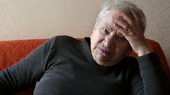 Depressed and worried old woman on the sofa Stock Footage
