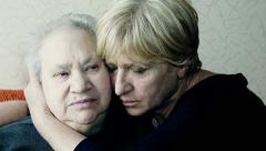 Senior woman embraces her old and sad mother on the sofa Stock Footage