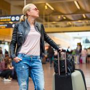 Female traveller checking flight departures board. Stock Photos