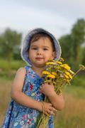 Cute little girl holding an bucket of yarrow flowers - stock photo