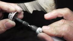 Goldsmith is polishing a gold or silver ring Stock Footage