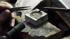 Goldsmith is creating a ring using a gas torch Stock Footage