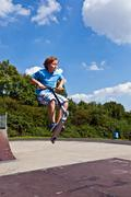 Young boy going airborne with his scooter Stock Photos