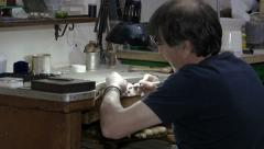 Stock Video Footage of goldsmith refines and polishes a silver cross with a polishing machine