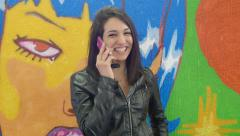 Young attractive woman talking at the mobile phone near a painted wall: murals Stock Footage