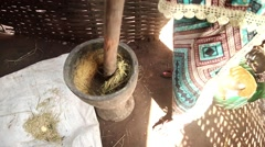 Woman smashing rice Africa village Stock Footage