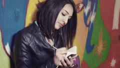 Young woman with notepad in the city: murals, sketches, colors, wall Stock Footage