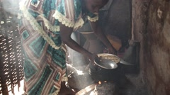 Woman cooking rice Africa village Stock Footage