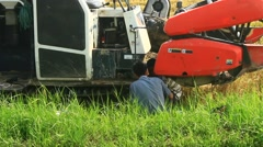 Farmers harvesting rice in the fields by machine Stock Footage