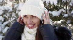 beautiful woman listening to music with headphones in park in winter - stock footage