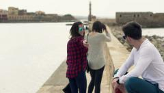 Group of friends walking through harbour by sea HD Stock Footage