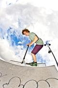 boy with scooter is going airborne - stock photo