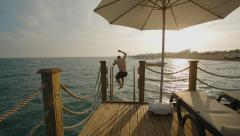 Young man jumping from a pier into the sea at sunset, sea resort - stock footage