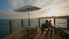 Young man relaxing on lounger on the pier of luxury hotel at sunset, sea resort Stock Footage