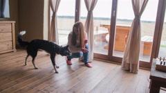 Girl teaches dog to follow finger 4K Stock Footage