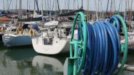Stock Video Footage of water hose at a marine with people and yachts in background