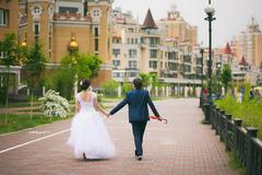 Wedding couple walking cheerfully in urban landscape. Bride and groom outside Stock Photos