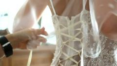 Lacing dress of bride. dressing up young bride for wedding ceremony. Stock Footage