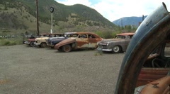 Old wrecks, cars 1950s on gravel lot, forgotten Stock Footage