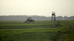 Green field with tractor plowing soil wide shot 4K Stock Footage