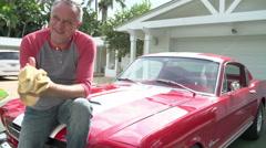 Retired Senior Man Sitting On Hood Of Restored Classic Car Stock Footage