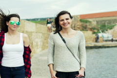 Two girlfriends talking and walking in harbour by sea NTSC Stock Footage