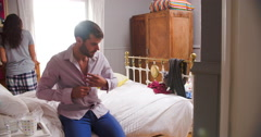 Couple Getting Dressed For Work In Bedroom Stock Footage