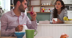 Young Couple Eating Breakfast In Kitchen Together Stock Footage