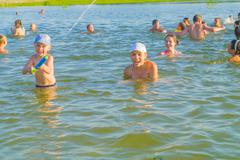It is a lot of children and teenagers cheerfully bathe in lake. - stock photo